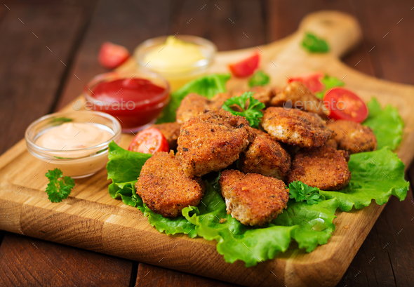 Chicken nuggets and sauce on a wooden background. - Stock Photo - Images