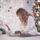 Christmas: a Young Lovely Woman Sits on a Bed Near a Christmas Tree and Prints on a Laptop - VideoHive Item for Sale