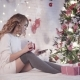 Young Beautiful Woman Sits on a Bed Near a Christmas Tree, Drinks Tea and Uses an Application - VideoHive Item for Sale