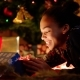 Black Teen Girl Is Openning Christmas Gift Box Under Decorated Christmas Tree - VideoHive Item for Sale