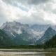 Clouds Are Moving Over the Peaks of the Alpine Mountains and a Mountain Lake - VideoHive Item for Sale