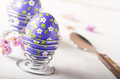 Wire egg cups with painted easter eggs on white table - PhotoDune Item for Sale