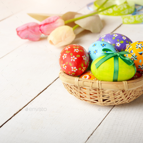 Rustic style painted easter eggs in basket on white table - Stock Photo - Images