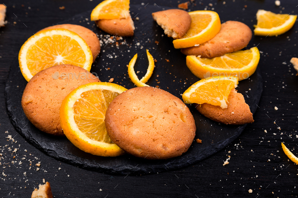 Cookies and orange citrus fruit on slate plate on black background - Stock Photo - Images