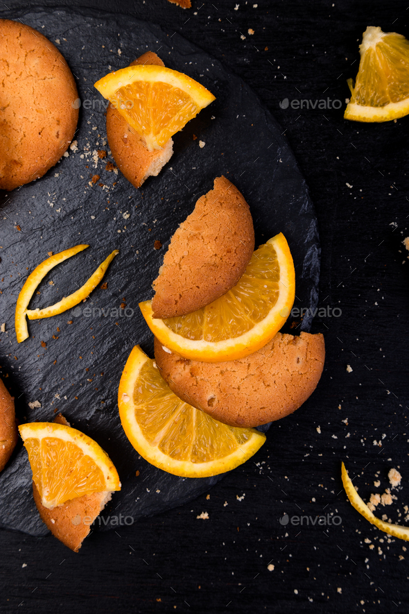 Cookies and orange citrus fruit on slate plate on black background. Flat lay - Stock Photo - Images