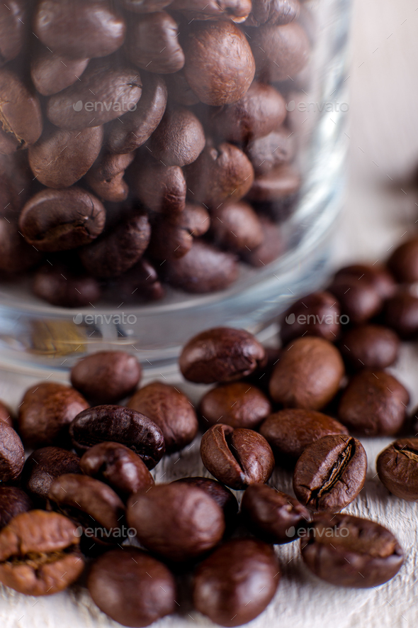 Coffee beans or grain in jar on white wooden background. Macro. - Stock Photo - Images