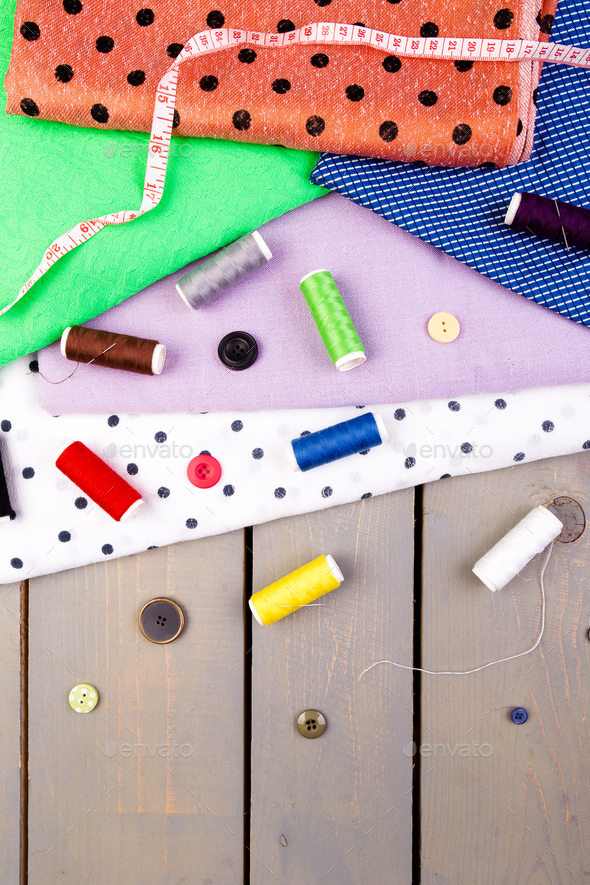 Items for sewing clothes. Sewing buttons, spools of thread and cloth. Top view. - Stock Photo - Images