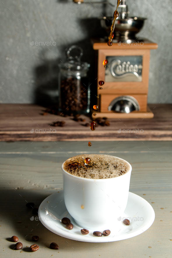 Pouring a Cup of Coffee Creating Splash on Wooden Background. - Stock Photo - Images