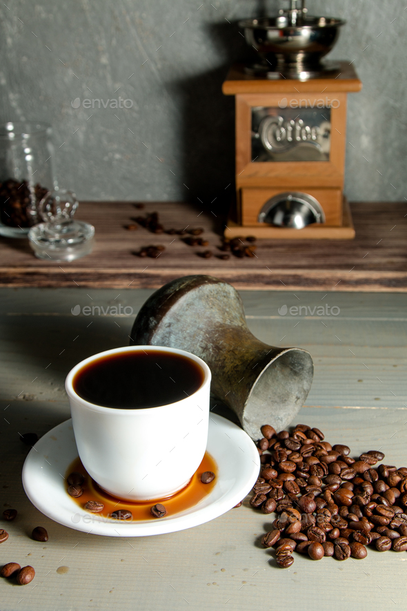 A White Cup of Hot Coffee in a Scattering of Coffee Beans on a Wooden Background - Stock Photo - Images