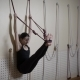 Beautiful Brunette Woman Is Hanging on the Ropes Leaning Agains the Wall in Yoga Centre