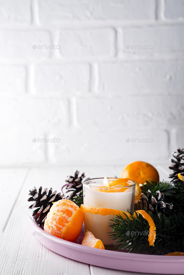 Christmas mandarines with lighted candle. - Stock Photo - Images