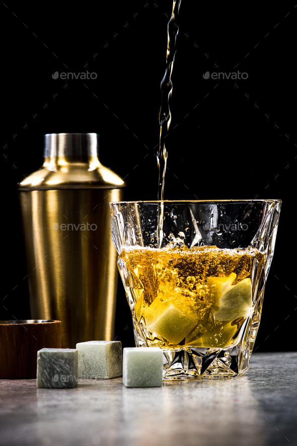 Pouring whisky or alcohol into crystal glass on bar - Stock Photo - Images
