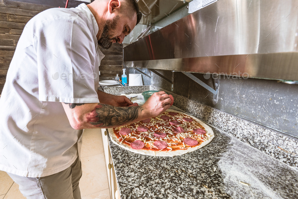Bearded man chef preparing pizza at local business - Stock Photo - Images