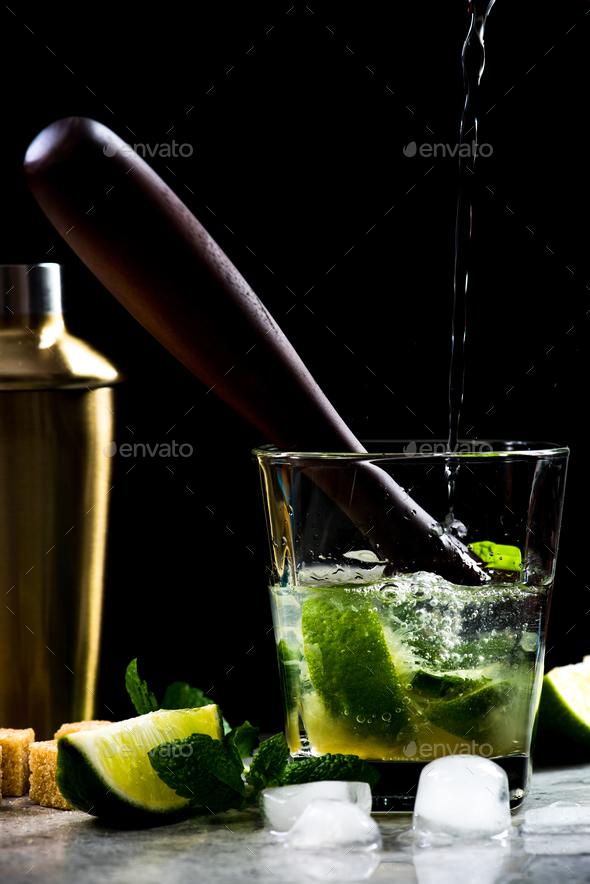 Pouring rum into Mojito cocktail on stone bar - Stock Photo - Images