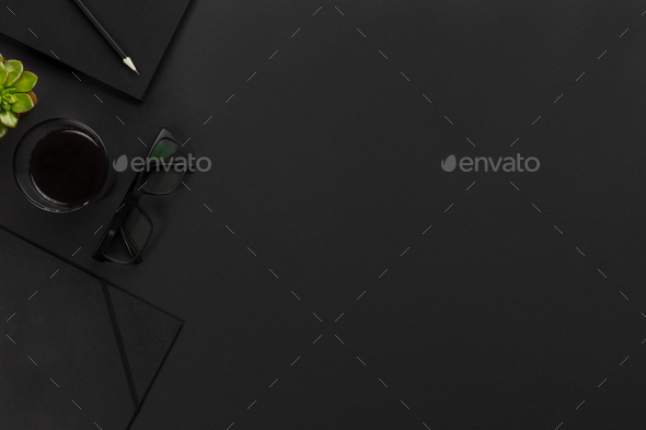 Top view of black office desk with notebook and supplies - Stock Photo - Images