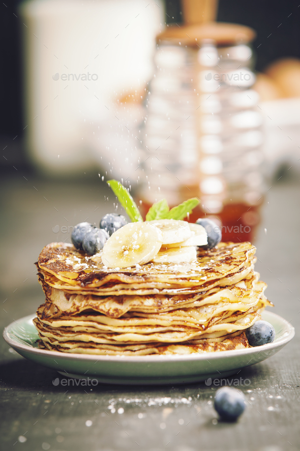 Homemade pancakes with fresh bananas, blueberries and honey - Stock Photo - Images