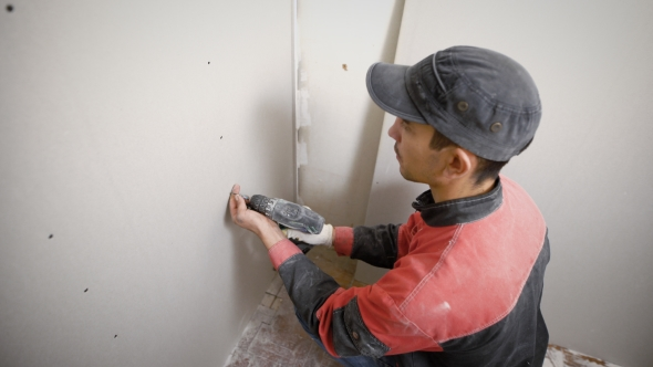 Concentrated Worker Making Holes in Wall with Drill Working on Site