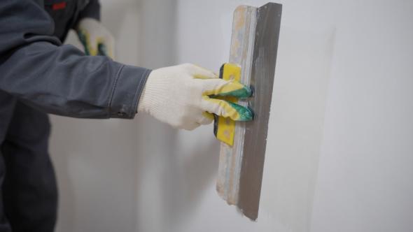 Crop Builder Applying Stucco on Wall Decorating Room Interior