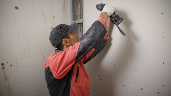 Builder in Uniform Installing Panels on Wall Using Electric Drill