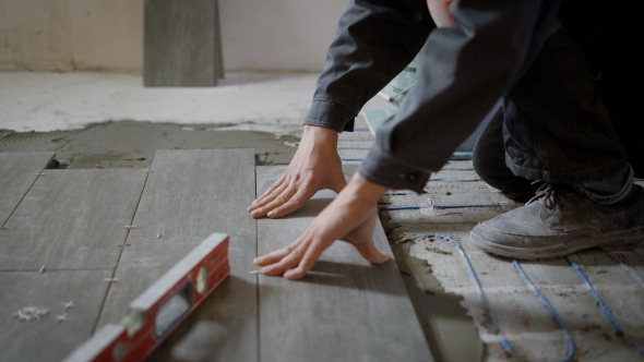 Man Working On Construction Site Laying Tiles On Floor With Cement
