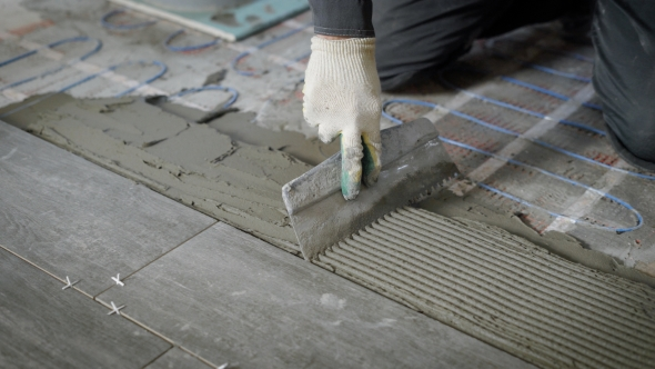 Anonymous Site Worker Applying Cement on Floor and Laying Tiles