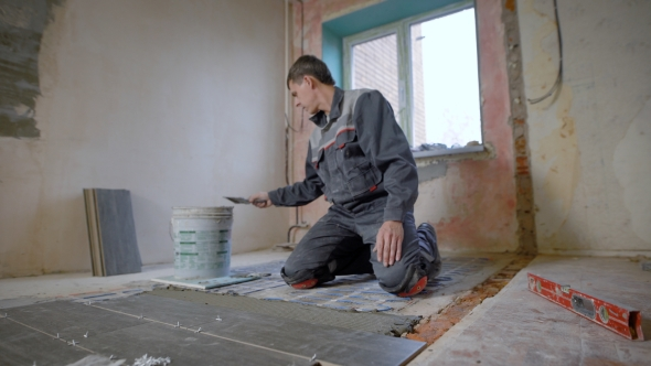 Man Working On Construction Site And Laying Tiles On Floor By Pampampam