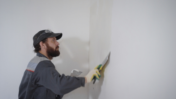 Professional Contractor Working and Smoothing Plaster on Wall with Spatula