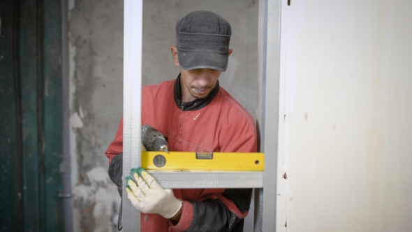 Professional Constructor Using Leveling Gauge for Measuring on Building Site