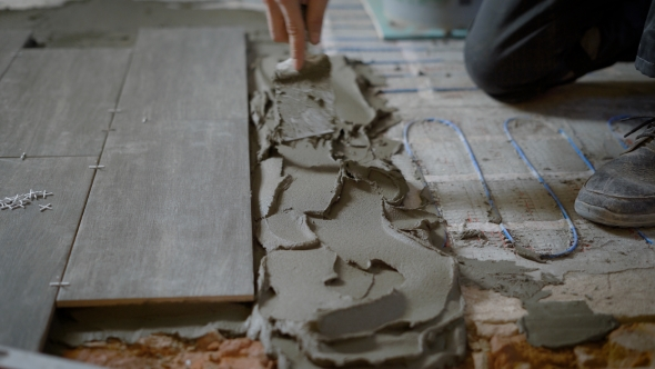 Anonymous Man Applying Cement on Floor While Working on Site