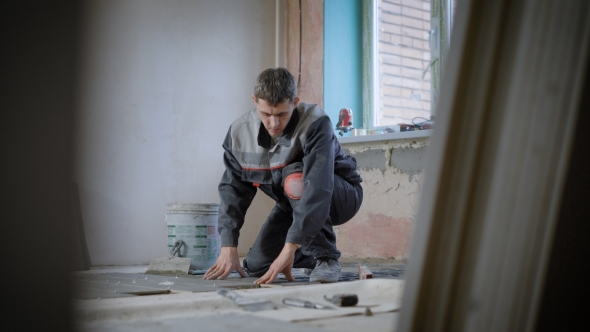 Concentrated Builder Decorating Floor in Room Under Construction with Tiles
