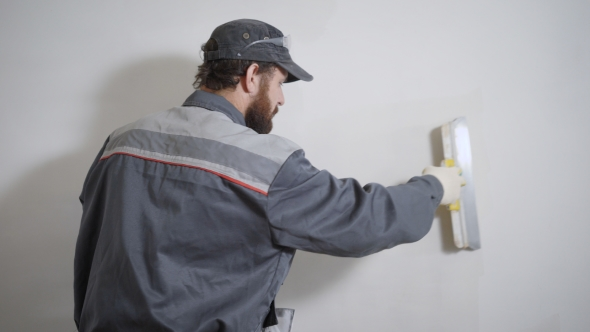Builder Working on Site and Smoothing Plaster on Wall with Pallet