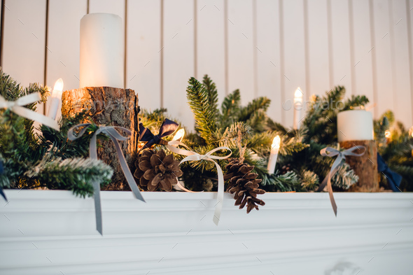 Christmas Fireplace, Xmas Lights Decoration, Tree Branches, candles and pine pieces - Stock Photo - Images
