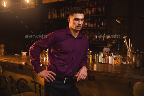 Young man in shirt standing at the bar counter - Stock Photo - Images