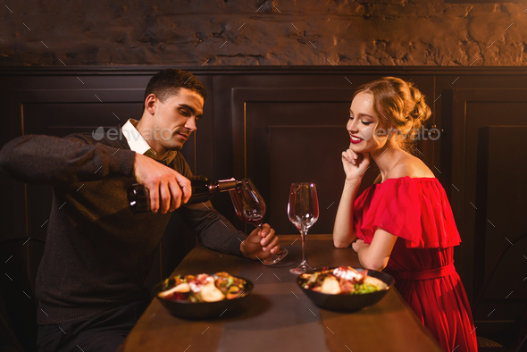 Man pours wine into a glass, couple in restaurant - Stock Photo - Images