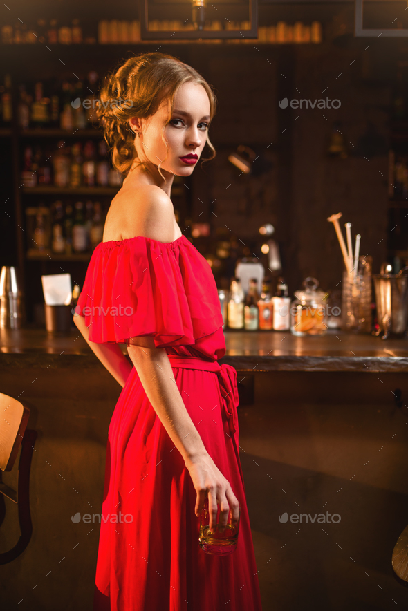 Woman in red dress standing at the bar counter - Stock Photo - Images