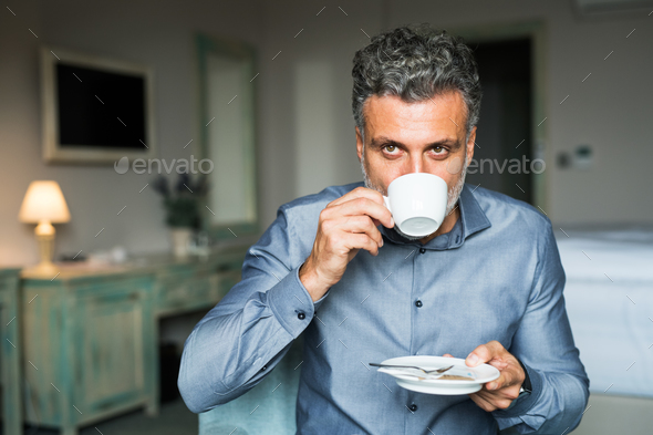 Mature businessman drinking coffee in a hotel room. - Stock Photo - Images