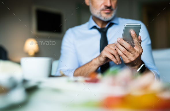 Mature businessman with smartphone in a hotel room. - Stock Photo - Images