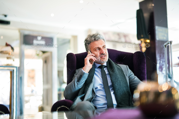 Mature businessman with smartphone in a hotel lounge. - Stock Photo - Images