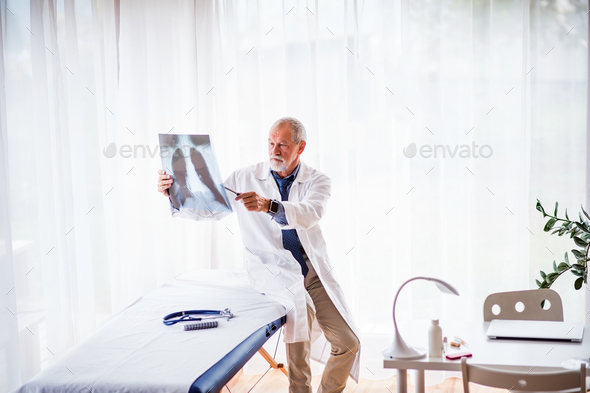 Senior doctor looking at chest x-ray in office. - Stock Photo - Images