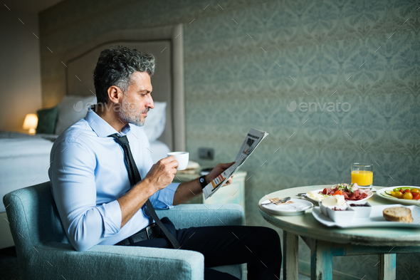 Mature businessman having breakfast in a hotel room. - Stock Photo - Images