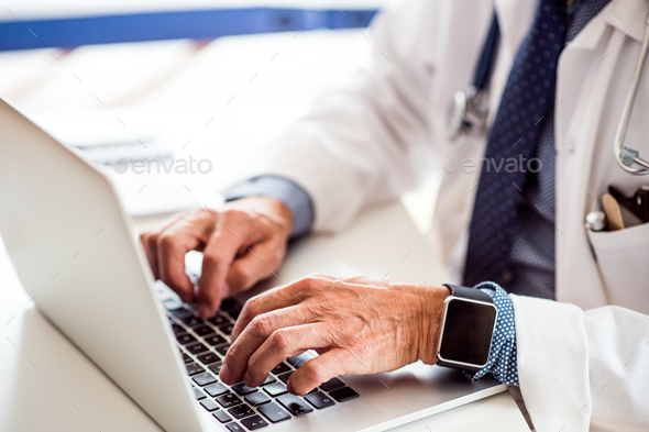 Senior doctor with laptop working at the office desk. - Stock Photo - Images