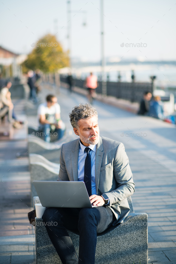 Mature businessman with laptop in a city. - Stock Photo - Images