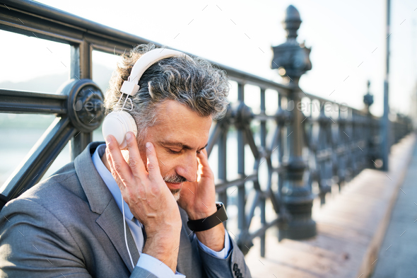 Mature businessman with headphones in a city. - Stock Photo - Images