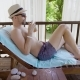 Young Man Is Wearing Summer Shorts, Straw Hat and Sunglasses, Is Relaxing on a Sunbed in a Tent and