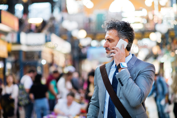 Mature businessman with smartphone in a city. - Stock Photo - Images