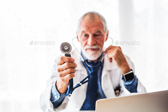 Senior doctor with laptop at the office desk. - Stock Photo - Images