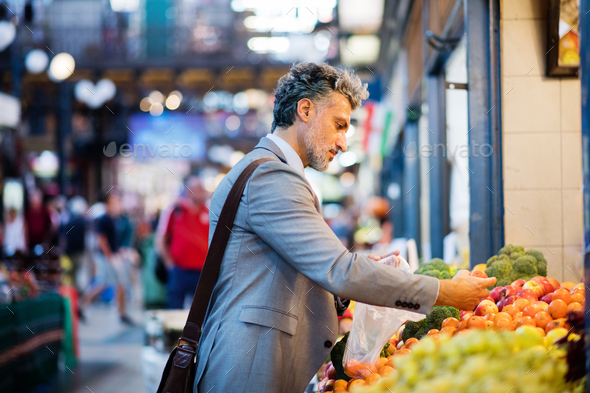 Mature businessman buying fruit in a city. - Stock Photo - Images