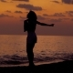 Silhouette of Happy Slim Woman Is Jumping on a Sea Coast in Evening Time After Sunset and Rising