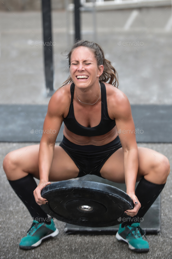 Woman lifting weights at a cross training competition - Stock Photo - Images