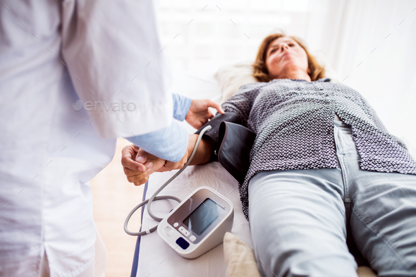 Female doctor checking blood pressure of a senior woman. - Stock Photo - Images